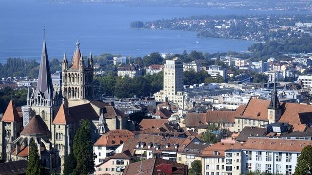 Blick auf die Gebäude der Stadt Lausanne mit der Kathedrale und dem See im Hintergrund.