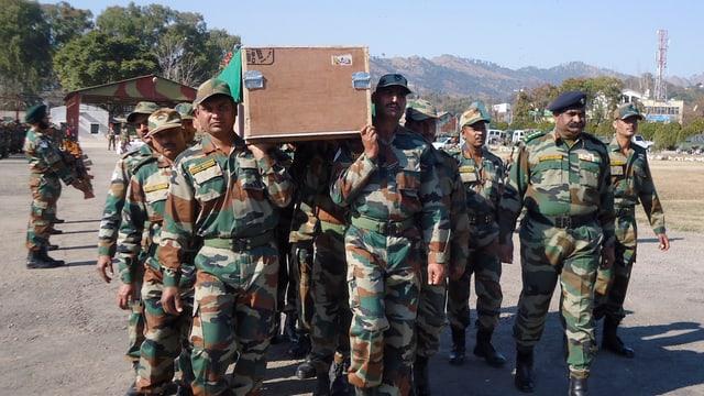 Indische Soldaten tragen einen Sarg auf den Schultern.