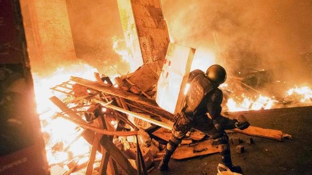 Ein Mensch in Kampfmontur steht an einer brennenden Barrikade.