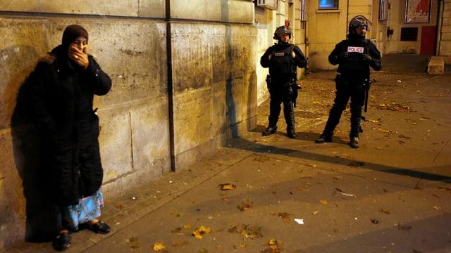 Zwei Polizisten in Vollmontur, daneben eine Frau mit Kopftuch, die die Hand vor den Mund hält.