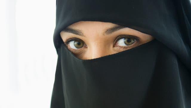 Augen einer Frau, die aus einem schwarzen Gesichtschleier schauen.