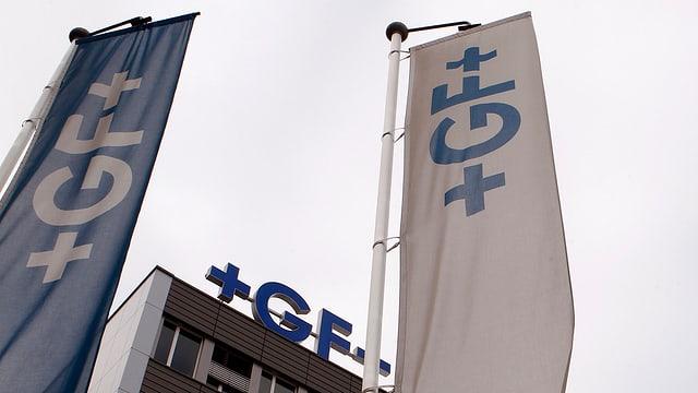 Ein Haus mit Georg-Fischer-Logo, davor Fahnen mit demselben Logo.
