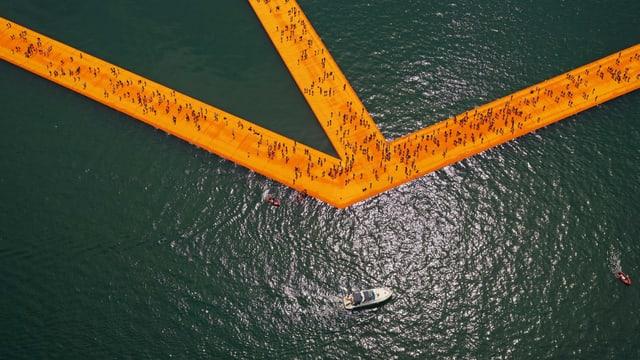 Ein oranger Steg auf einem See. Auf dem Steg laufen viele Leute.