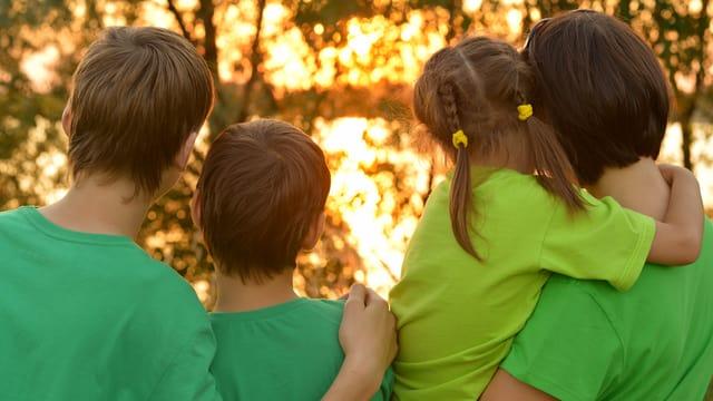 Kinder mit Mutter blicken in den Sonnenuntergang