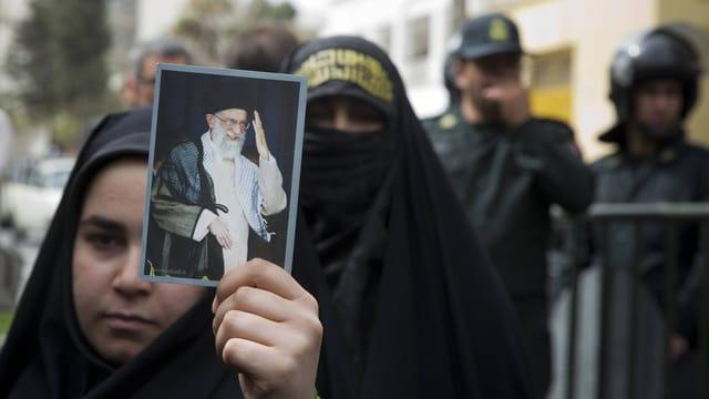 Eine schwarz gekleidete Frau hält ein Foto des höchsten Geistlichen, Ali Chamenei, in die Höhe, im Hintergrund Polizisten.