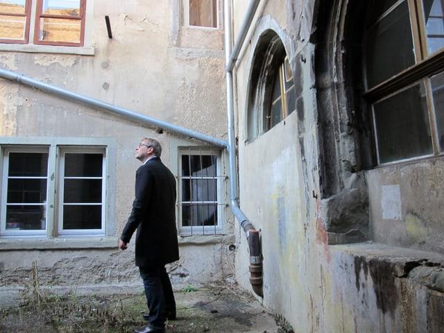 Stadtrat Daniel Preisig sieht sich im Innenhof des Stadthausgevierts die Fassaden der baufälligen Häuser an.