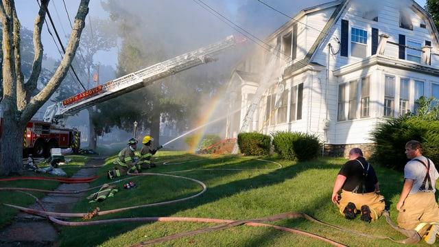 Feuerwehrleute an einem qualmenden Haus