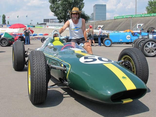 Ein grüner Lotus 24 Rennwagen, darauf ein Mann mit Cowboy Hut