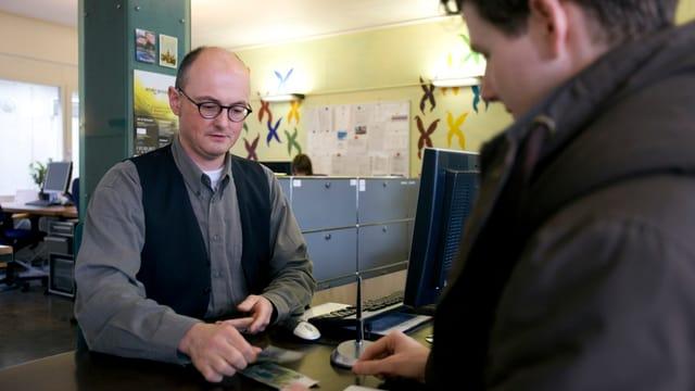 Ein Bankmitarbeiter gibt einem Kunden Geld heraus, aufgenommen im März 2008.