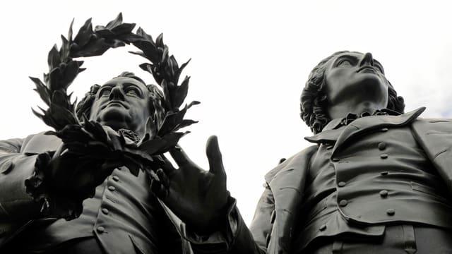Sicht von unten auf die Statuen von Goethe und Schiller. Goethes Kopf ist durch einen Lorbeerkranz hindurch zu sehen.