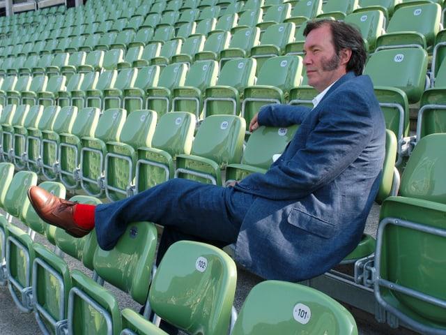 David Pountney sitzt in den grünen Schalenstühle der Seebühne, in blauem Anzug, einen Fuss mit roten Socken über die vordere Sitzreihe gelegt.