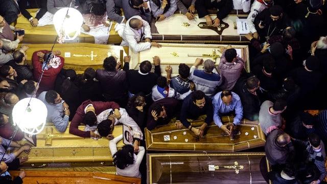 Christen beugen sich verzweiflet über Sarge mit den Opfern der Terroranschläge
