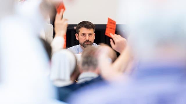Ein Mann sitzt vor Menschen, die rote Zettel in die Luft halten.