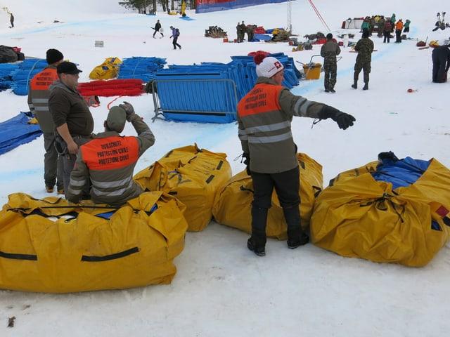 Mitglieder des Zivilschutzes schnüren Pakete mit Rolzäunen und Banden.