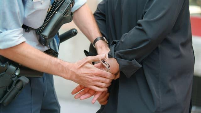 Ein Polizist legt einem Mann Handschellen um die Handgelenke.