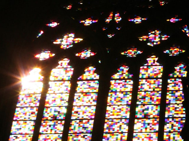 Licht fällt durch die farbigen Riesenfenster einer Kirche.