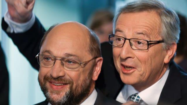 Juncker steht hinter Schulz und hält die rechte Faust in die Luft.