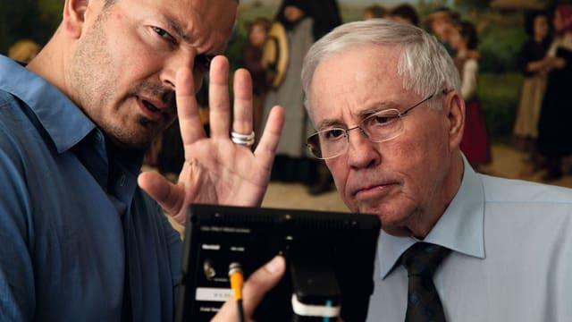 Zwei Männer blicken konzentriert in einen kleinen Bildschirm, den der eine in der Hand hält.