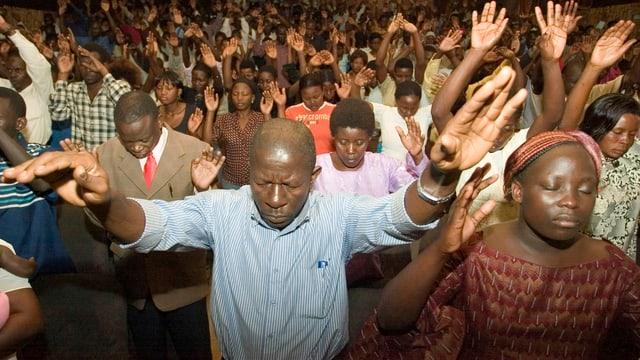 Menschen beim Beten. Sie halten die Hände in die Höhe.