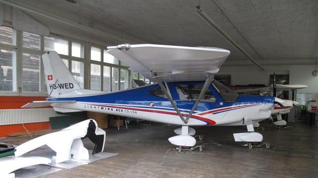 Ein kleines blauweisses Leichtflugzeug in einer Montagehalle.