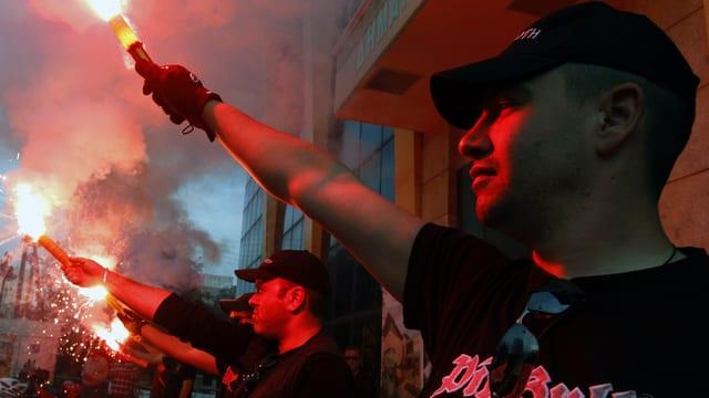 Mitglieder der Partei «Goldene Morgenröte» werben mit Leuchtkörpern vor dem Stadthausvon Perama. (reuters)