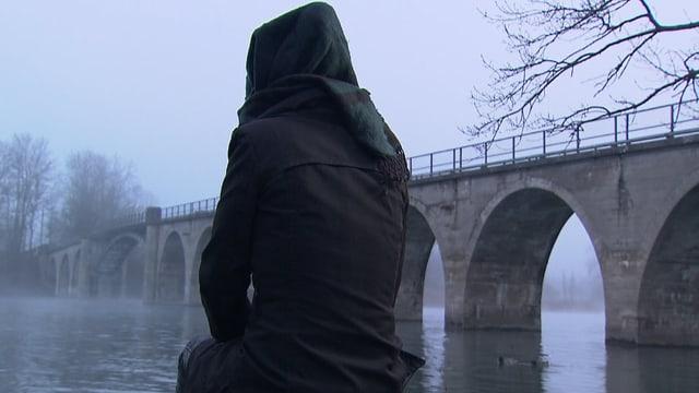 Eine Frau mit Kapuze sitzend an einem Fluss.