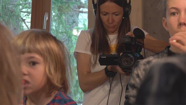 Petra Rothmund cun la camera da filmar ed enturn ils uffants.
