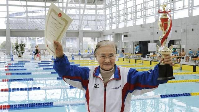 Die 100 Jahre alte Japanerin Mieko Nagaoka zeigt ihr Zertifikat und ihren Pokal vor dem Schwimmbecken in Tokio. (Twitter.com/nbcolympics)