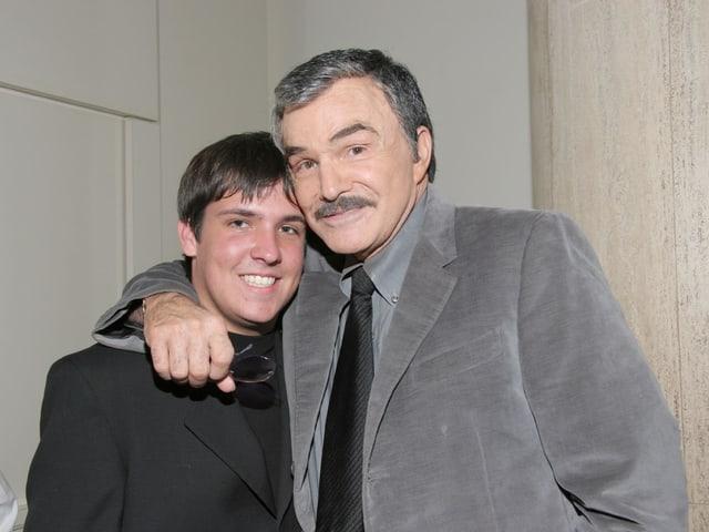 Burt Reynolds umarmt seinen Sohn und beide tragen einen Anzug.