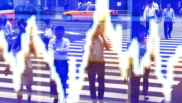 Menschen werden auf einer Tafel reflektiert, die eine Grafik des Wechselkurses zwischen dem japanischen Yen und dem US-Dollar außerhalb einer Maklerfirma in Tokio zeigt.