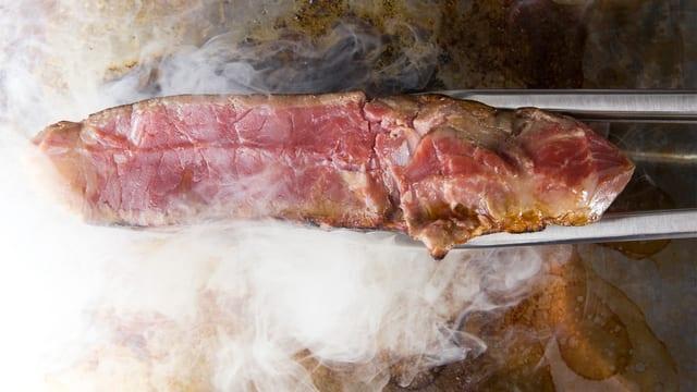 Ein heiss angebratenes Steak über dem Rost