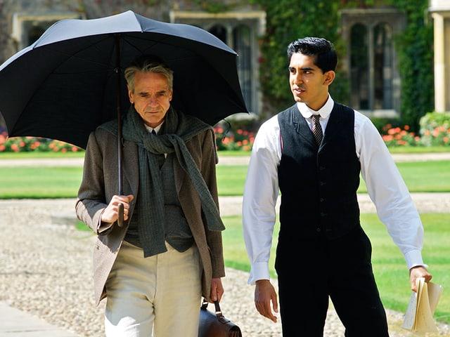 Zwei Männer laufen durch eine Parkanlage; links Prof. Hardy mit Regenschirm, rechts Ramanujan im Anzug.
