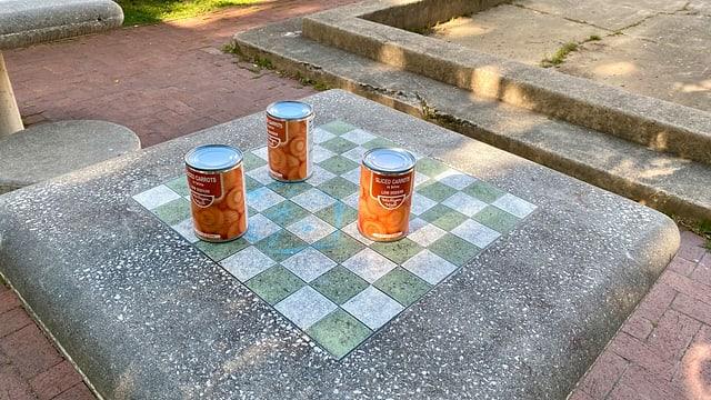 Auf einem Schachtisch hat jemand eine bescheidene Lebensmittel-Spende hinterlassen. Karottenbüchsen statt Schachfiguren.