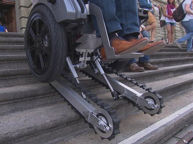 Ein Rollstuhl mit darunter gebauten Raupen fährt rückwärts eine Treppe hinauf.