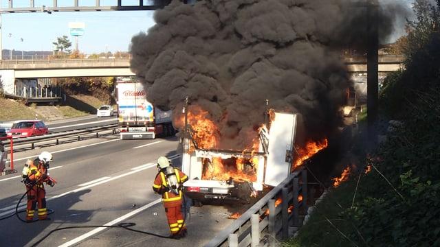 Feuerwehrleute hinter einem brennenden und stark rauchenden Lieferwagen