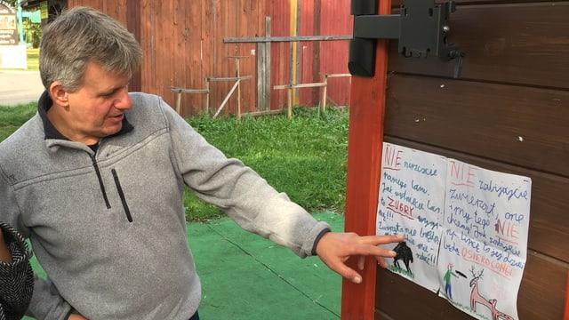 Mann zeigt auf Kinderzeichnung an Wand.