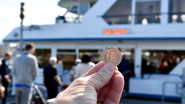 Eine Hand hält einen Fünfliber hoch. Im Hintergrund ein Zürichsee-Schiff
