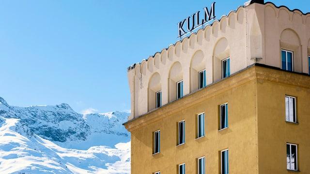 Hotel «Kulm» in St. Moritz vor einer Nebelkulisse und einem blauen Himmel.