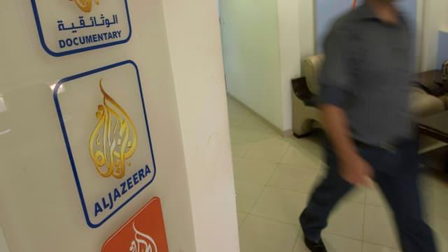 Logo von Al-Dschasira. Im Hintergrund Silhouette eines Mannes.
