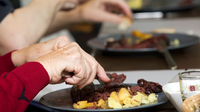 Hände einer älteren Person über einem Teller mit Wild.