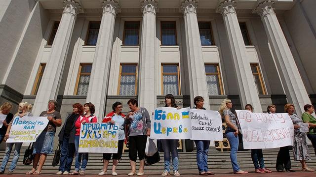 Personen stehen mit Plakaten vor einem Gebäude mit einer Treppe und Säulen.