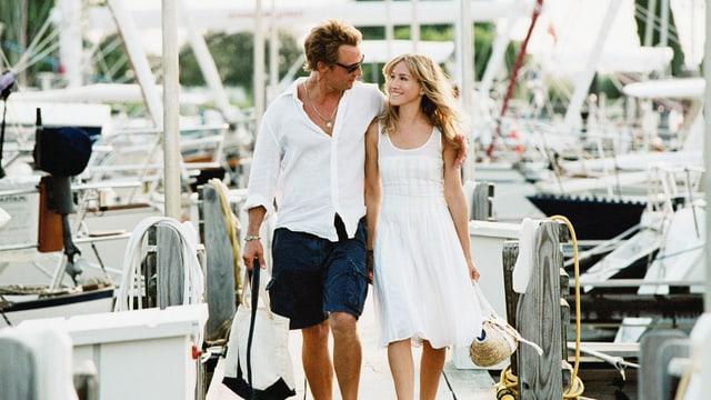 Ein junges Paar schlendert durch einen Yachthafen.