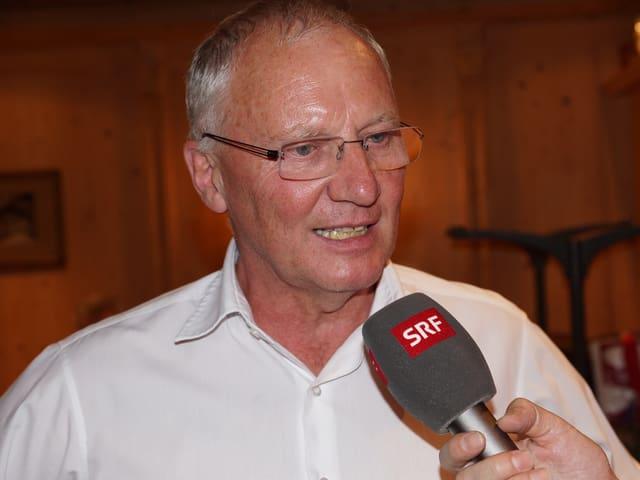 Emil Meier trägt ein weisses Hemd und eine Brille und gibt am Mikrofon Antworten auf die Fragen des Moderators.