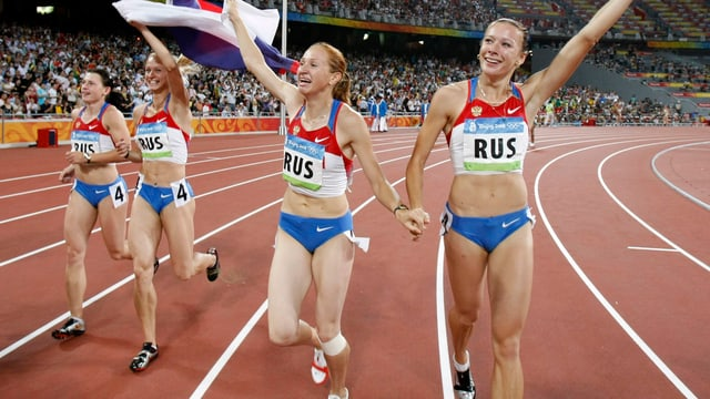 Vier russische Leichtathletinnen gehen durchs Stadion an den Olympischen Spielen in Peking