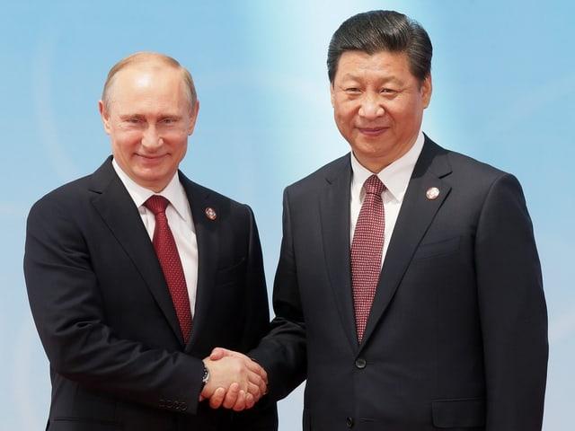 Putin und Xinping geben sich die Hand.