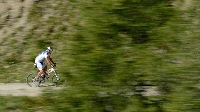 Ein Mountainbiker fährt auf einem Kiesweg.