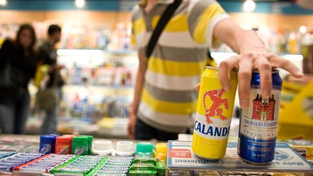 Ein junger Mann kauft zwei Dosen Bier