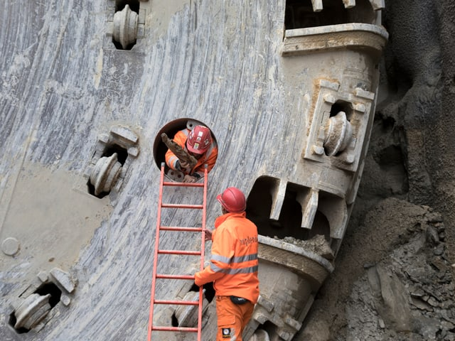 Mann in Arbeitskleidung kriecht durch ein Loch.