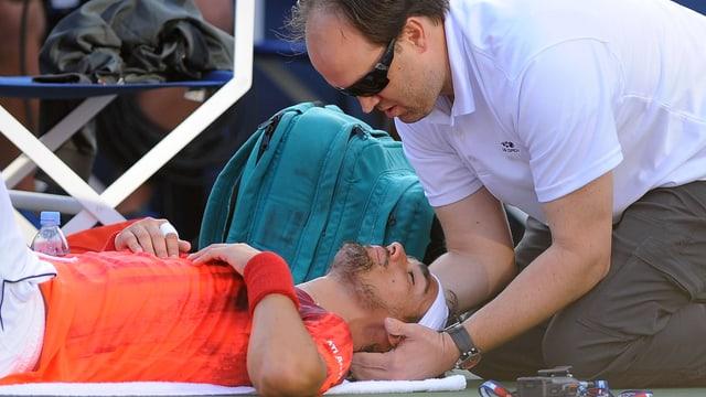 Fabio Fognini liegt am Boden und muss sich vom Physiotherapeuten am Rücken behandeln lassen.