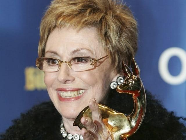 Eine Frau mit hält eine Auszeichnung in der Hand.